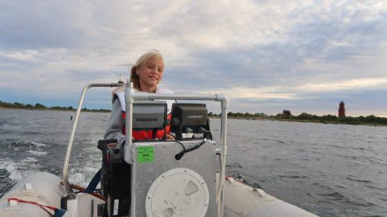 Iiris ajelee pikkuveneellä, taustalla Rönnskärin poogi